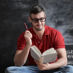 man-in-red-polo-shirt-and-blue-denim-jeans-holding-red-pen-3779488.jpg